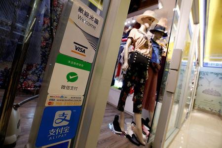 Labels of digital payment are displayed outside a boutique at a shopping mall in Hong Kong