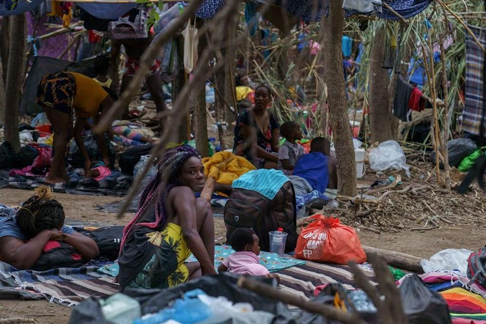 Haitian migrants are pictured in a makeshift encampment where more than 12,000 people hoping to enter the United States await under the international bridge in Del Rio, Texas on 21 September 2021 (AFP via Getty Images)
