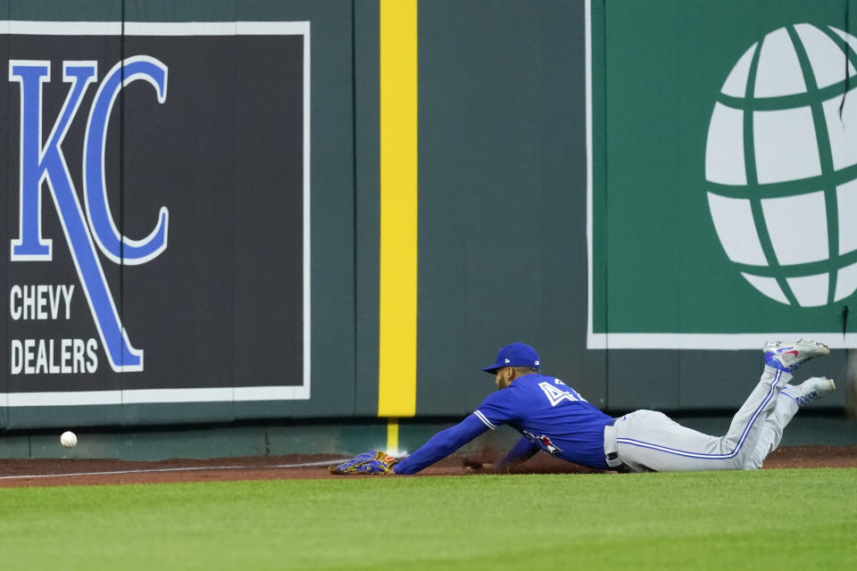 Toronto Blue Jays left fielder Lourdes Gurriel Jr. chases an RBI-triple by Kansas City Royals' Nicky Lopez during the third inning of a baseball game Thursday, April 15, 2021, in Kansas City, Mo. (AP Photo/Charlie Riedel)