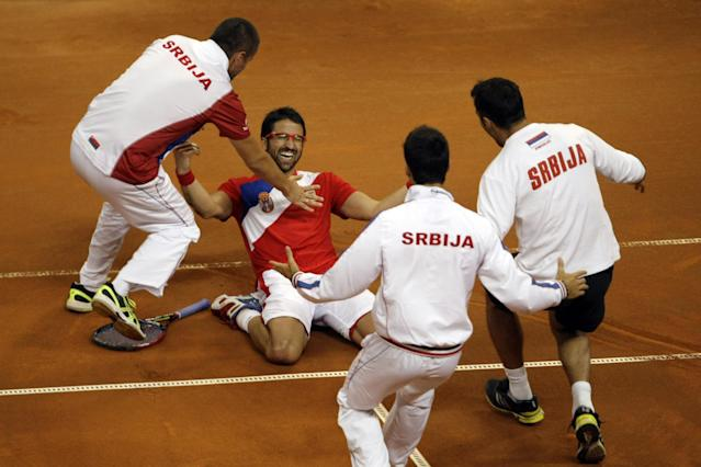 Serbia's Janko Tipsarevic, 2nd left, and his teammates celebrate their victory against Canada's national tennis team at the Davis Cup semifinals in Belgrade, Serbia, Sunday, Sept. 15, 2013. (AP Photo/ Marko Drobnjakovic)