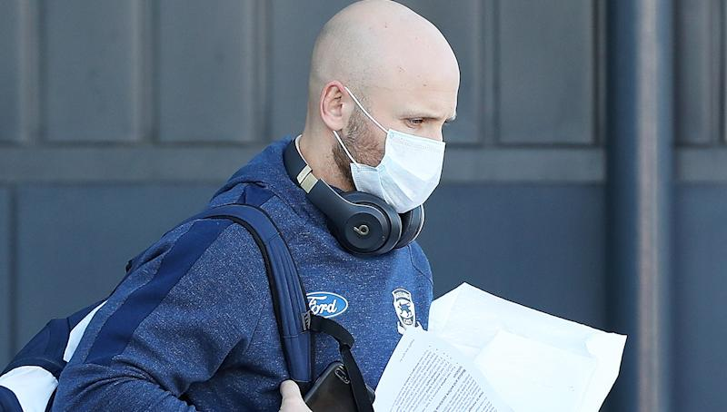 Gary Ablett Jr is pictured walking and wearing a face mask.