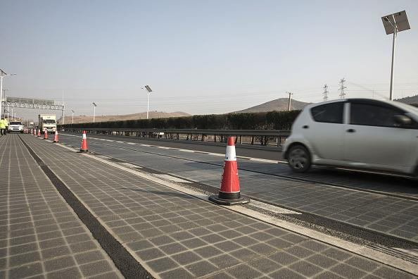 Vehicles travel on photovoltaic lanes developed by Qilu Transportation Development Group Co. on a highway in Jinan, China. About 45,000 vehicles barrel over the 3,540-foot-long section every day, and the solar panels inside generate enough electricity to power highway lights and 800 homes, according to Qilu Transportation. Photographer: Qilai Shen/Bloomberg