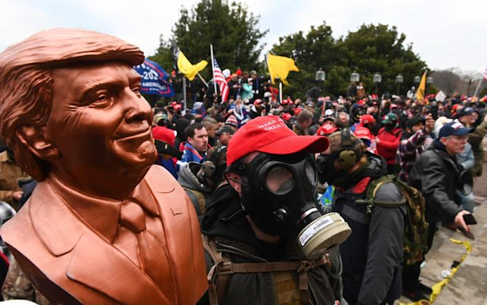 A supporter of US President Donald Trump wears a gas mask and holds a bust of him after he and hundreds of others stormed stormed the Capitol building - Roberto Schmidt/AFP