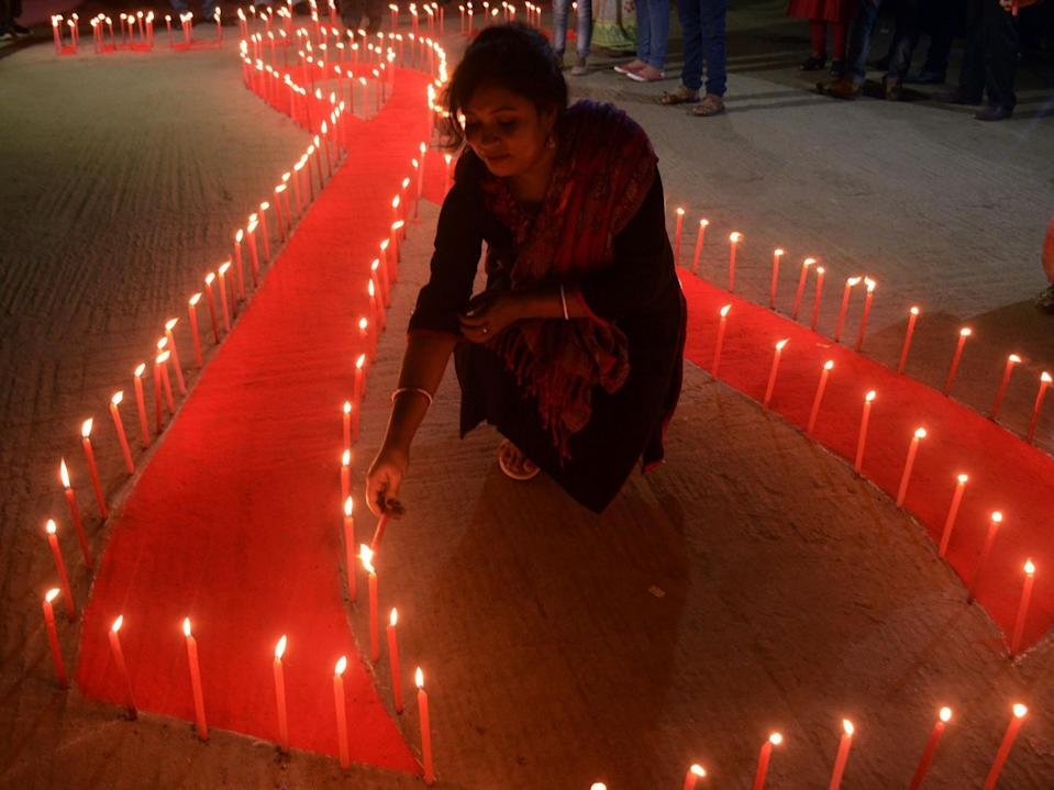 An Indian NGO volunteer lights candles placed on the ground in the shape of a red ribbon during an awareness rally on the eve of World Aids Day in Agartala, the capital of the northeastern state of Tripura, on 30 November 2017 (Arindam Dey/AFP/Getty)