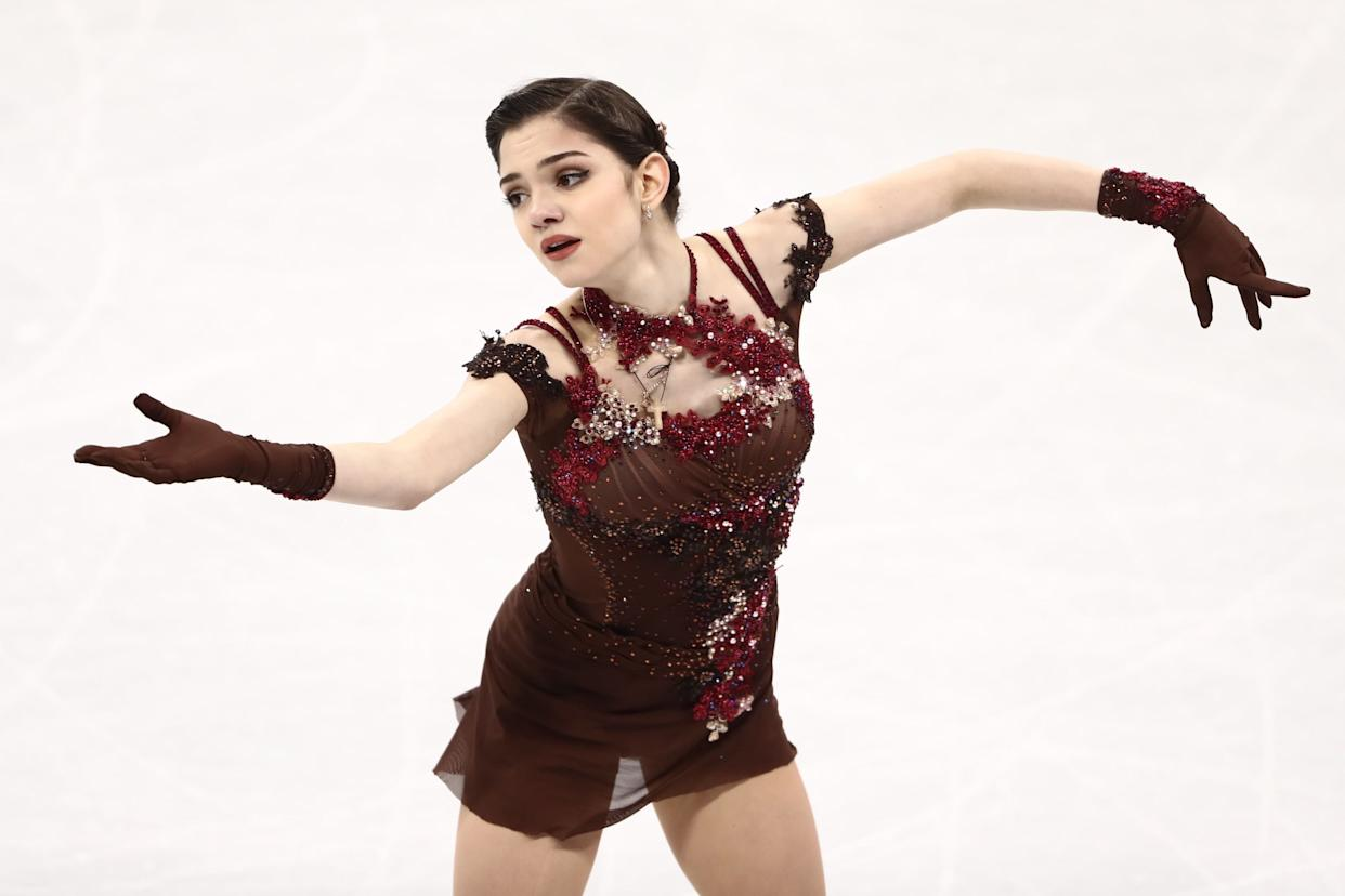 """Medvedeva, of Russia, wore this beautiful costume (which is <a href=""""https://www.vogue.com/fashion-shows/fall-2008-ready-to-wear/rodarte/slideshow/collection#35"""" rel=""""nofollow noopener"""" target=""""_blank"""" data-ylk=""""slk:also giving us Rodarte vibes"""" class=""""link rapid-noclick-resp"""">also giving us Rodarte vibes</a>) for her free skate. The color and embellishments are beautiful, and the gloves add that extra special touch."""