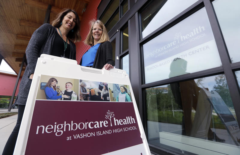 In this photo taken Wednesday, May 15, 2019, Neighborcare Health clinic manager Stephanie Keller, left, stands with Vashon Island High School nurse Sarah Day at the school campus clinic, where top service provided at the student-based health center is vaccinations, in Vashon Island, Wash. The idyllic island near Seattle known for its counterculture lifestyle and low immunization rates is seeing an increase in the number of children vaccinated for measles and other diseases. Keller said the center has received a spike in calls from concerned parents as Washington state struggles to contain a measles outbreak (AP Photo/Elaine Thompson)