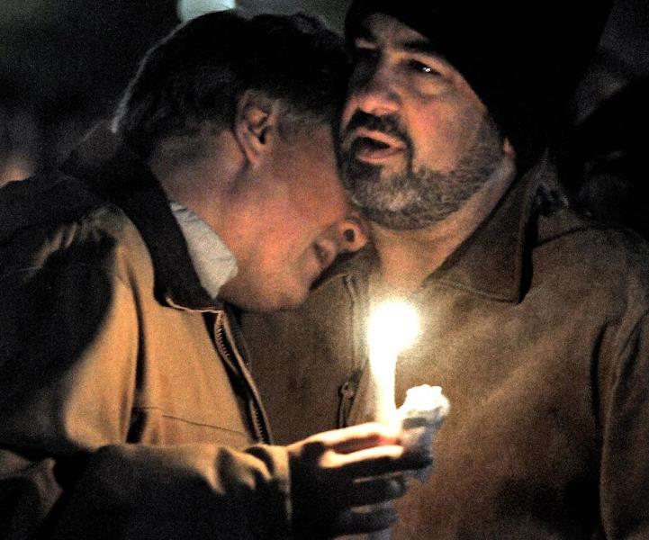 "Robert Marriott, father of Lizzi Marriott, is consoled by former co-worker, Paul Campaniello of Shrewsbury, as hundreds of friends and family members attended an emotional candlelight vigil on Saturday night, Oct. 13, 2012, at the Bay State Commons, for his daughter, Elizabeth ""Lizzi"" Marriott of Westboro, a University of New Hampshire student, who disappeared earlier in the week. Marriott is believed to be dead, and a man has been charged with second-degree murder. (AP Photo/Steve Lanava, Worcester Telegram & Gazette)"