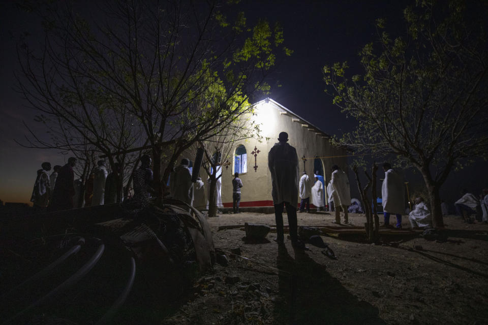 Tigrayan refugee Abraha Kinfe Gebremariam, 40, center, prays at a church early in the morning in Hamdayet, eastern Sudan, near the border with Ethiopia, on March 21, 2021. (AP Photo/Nariman El-Mofty)