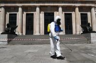 A member of the Spanish Emergency Military Unit (UME) wearing a full personal protective equipment disinfects outside the Archaeological Museum in Madrid