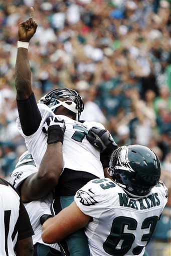 Philadelphia Eagles' Michael Vick, center, and Danny Watkins celebrate after Vick's rushing touchdown in the second half of an NFL football game against the Baltimore Ravens, Sunday, Sept. 16, 2012, in Philadelphia. The Eagles won 24-23. (AP Photo/Mel Evans)