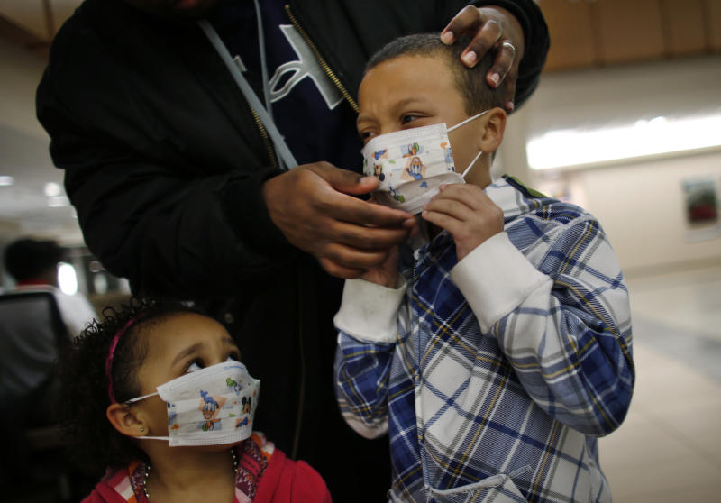 Here Damien Dancy puts masks on his children Damaya, 3, left, and Damien, 7, on Wednesday, Jan. 9, 2013 at Sentara Princess Anne Hospital in Virginia Beach, Va.   Hospitals in Hampton Roads are urging patients and visitors to wear a mask at their facilities to help stop the spread of the flu. The recommendation was issued Wednesday by more than two dozen medical centers. In a joint statement, the hospitals said the recommendation applies to hospitals, urgent care centers and branch clinics, among others. (AP Photo/The Virginian-Pilot, Stephen M. Katz)