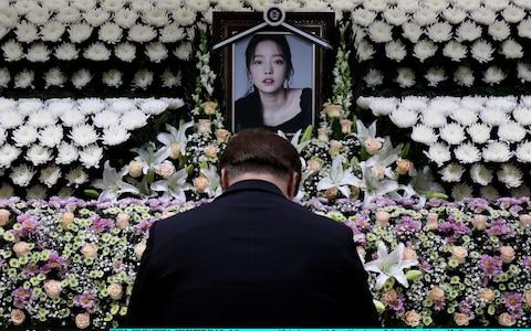 A South Korean man pays tribute at a memorial altar as his makes a call of condolence in honor of the K-pop star Goo Hara at the Seoul St. Mary's Hospital - Credit: Getty