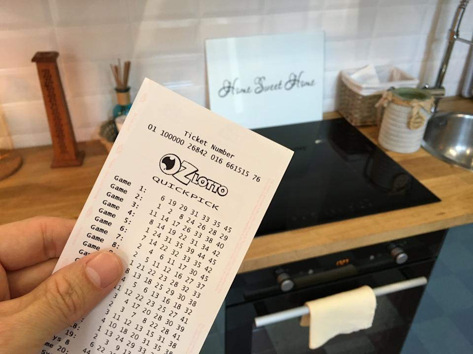 A man holds an OzLotto ticket in his kitchen