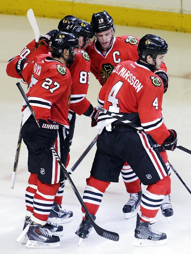 Chicago Blackhawks' Jonathan Toews (19) celebrates with teammates after scoring a goal against the Minnesota Wild during the third period in Game 5 of an NHL hockey second-round playoff series in Chicago, Sunday, May 11, 2014. The Blackhawks won 2-1. (AP Photo/Nam Y. Huh)