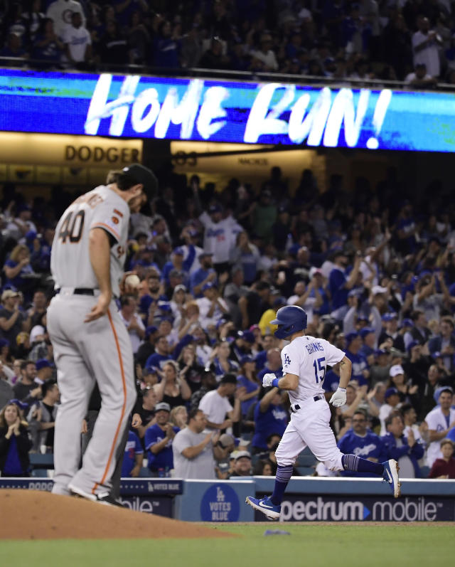 Los Angeles Dodgers' Austin Barnes, right, rounds third after hitting a two-run home run off San Francisco Giants starting pitcher Madison Bumgarner, left, during the fourth inning of a baseball game Thursday, June 20, 2019, in Los Angeles. (AP Photo/Mark J. Terrill)
