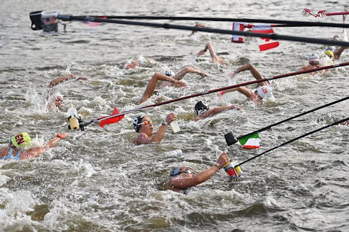 <p>TOPSHOT - Italy's Rachele Bruni (C) takes refreshment at a feed station along the course during the women's 10km marathon swimming event during the Tokyo 2020 Olympic Games at the Odaiba Marine Park in Tokyo on August 4, 2021. (Photo by Oli SCARFF / AFP) (Photo by OLI SCARFF/AFP via Getty Images)</p>