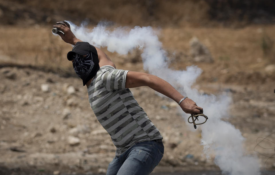 A Palestinian demonstrator throws back a teargas canister during clashes with Israeli forces at the Hawara checkpoint, south of the West Bank city of Nablus Friday, May 21, 2021. (AP Photo/Majdi Mohammed)