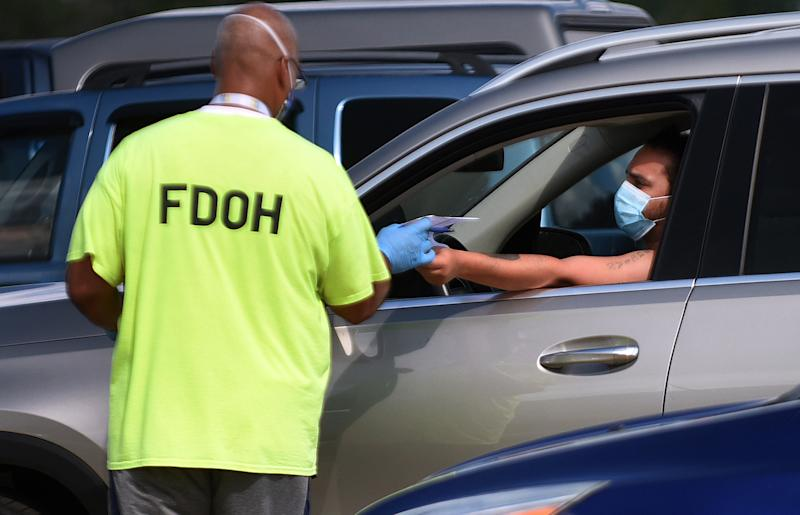 KISSIMMEE, FLORIDA, UNITED STATES - 2020/07/14: A health department worker checks in a man wearing a mask to be tested for COVID-19 at a drive through testing site at Osceola Heritage Park. Florida continues to be a hot spot for coronavirus cases and the demand for testing also remains high with over 600 people visiting this site today. (Photo by Paul Hennessy/SOPA Images/LightRocket via Getty Images)