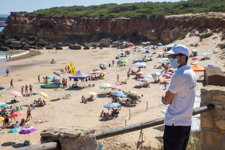 CONIL DE LA FRONTERA, SPAIN - JUNE 28: An assistant observes the beach of Cala del Aceite to control overcrowding on June 28, 2020 in Conil de la frontera, Spain.On June 21 the Government announced the end of the alarm state relating to Covid-19. (Photo by Juan Carlos Toro/Getty Images)