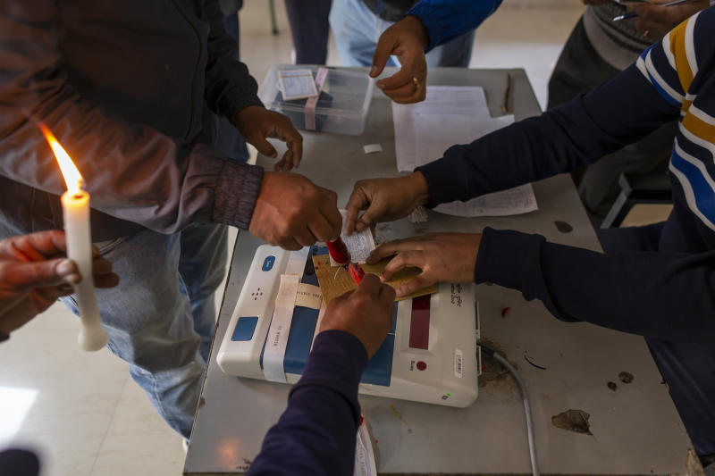 Election officials and observers seal a polling apparatus at a polling booth before the booth opened for a bypoll for an assembly seat in Dharmsala, India, Monday, Oct. 21, 2019. The seat was vacated by Kishan Kapoor, a Bharatiya Janata Party member of legislative assembly , who was elected to the Lok Sabha in May as voting is underway in two Indian states of Maharashtra in the west and Haryana in the north where the Hindu nationalist Bharatiya Janata Party (BJP) headed by prime minister Narendra Modi is trying to win a second consecutive term.  (AP Photo/Ashwini Bhatia)