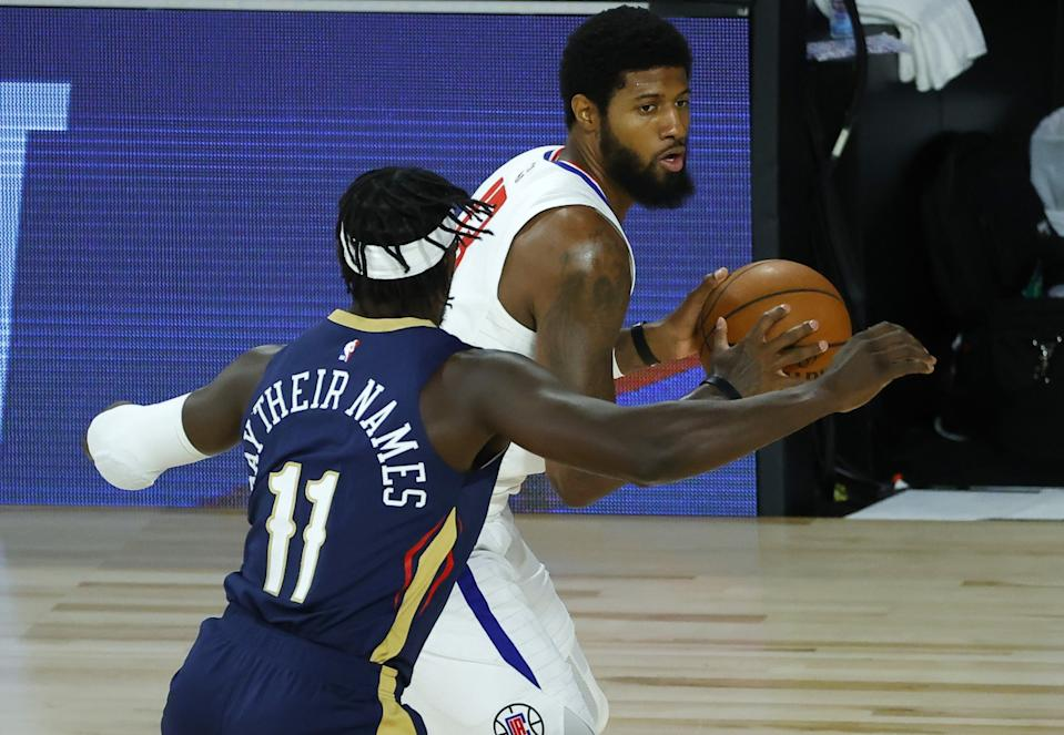 Clippers' Paul George drives past New Orleans Pelicans' Jrue Holiday during the first half.