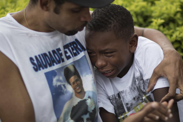 A boy is comforted by a friend wearing a shirt with a photo of Douglas Rafael da Silva Pereira, during Pareira's burial in Rio de Janeiro, Brazil, Thursday, April 24, 2014. A protest followed the burial of Douglas Pereira, whose shooting death sparked clashes Tuesday night between police and residents of the Pavao-Pavaozinho slum. (AP Photo/Felipe Dana)