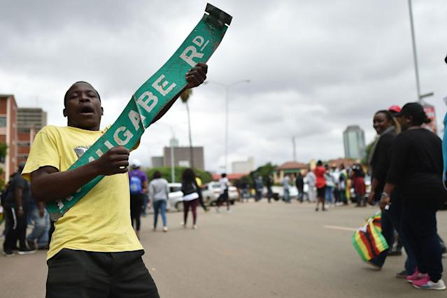 "<p>A man reacts with a sign reading ""Robert Mugabe Road"" during a demonstration marching towards the State House while demanding the resignation of Zimbabwe's president on Nov. 18, 2017 in Harare. (Photo: AFP/Getty Images) </p>"