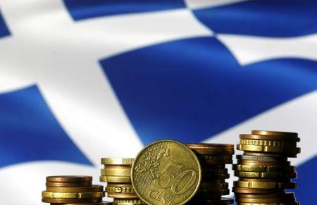 Euro coins are seen in front of a displayed Greece flag in this picture illustration