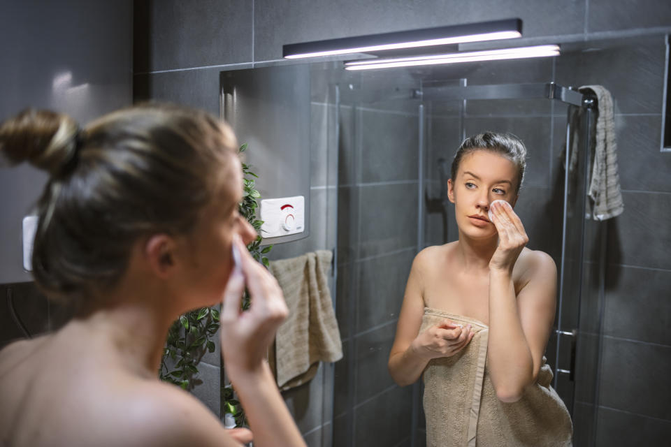 Young woman in bathrobe looking in bathroom mirror. Portrait of beautiful girl in bathrobe and with towel cleaning her face with sponge and smiling, standing in bathoom.