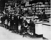 <p>A group of children stand in line as they wait to collect a loaf of bread from a local shopkeeper during a coal strike.</p>