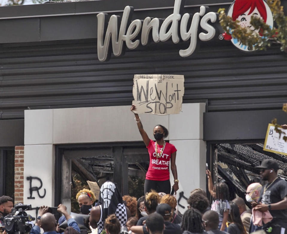 People hold a rally at Wendy's on University Avenue in Atlanta on Sunday, June 14, 2020. Rayshard Brooks died after a confrontation with police officers at the fast food restaurant in Atlanta on Friday. (Alyssa Pointer/Atlanta Journal-Constitution via AP)