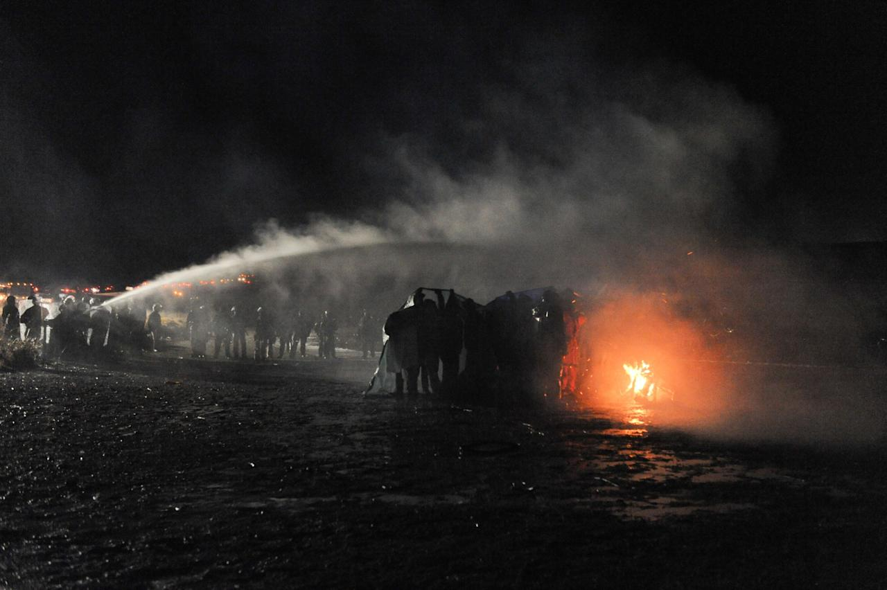 <p>Police use a water cannon to put out a fire started by protesters during a protest against plans to pass the Dakota Access pipeline near the Standing Rock Indian Reservation, near Cannon Ball, North Dakota, U.S. November 20, 2016. (Stephanie Keith/Reuters) </p>