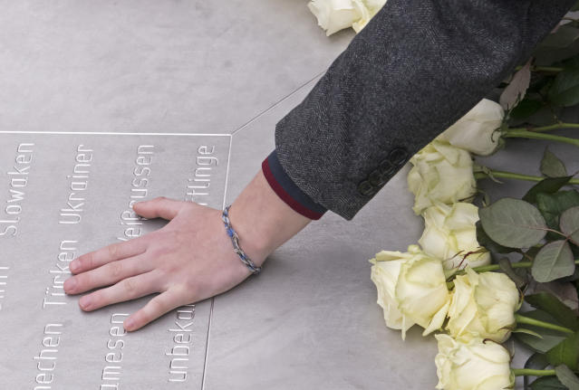 <p>A woman holds her hand on a plain metal plaque during a wreath-laying ceremony on occasion of the international Holocaust remembrance day in the former Nazi concentration camp Buchenwald near Weimar, Germany, Friday, Jan. 26, 2018. (Photo: Jens Meyer/AP) </p>