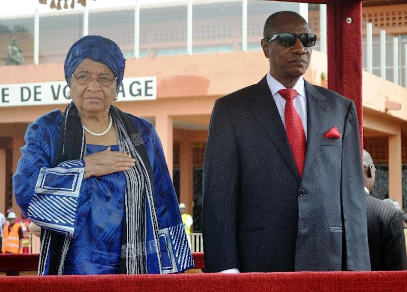 Guinea's President Alpha Conde (R) welcomes his Liberian counterpart Ellen Johnson Sirleaf on August 1, 2014 at Conakry's airport prior to a summit to tackle Ebola