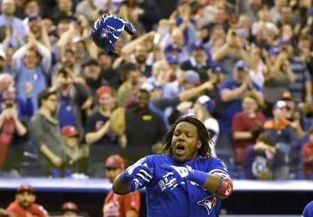 Mar 27, 2018; Montreal, Quebec, CAN; Toronto Blue Jays infielder Vladimir Guerrero Jr. (27) reacts after hitting a home run in the ninth inning to defeat the St. Louis Cardinals at Olympic Stadium. Mandatory Credit: Eric Bolte-USA TODAY Sports