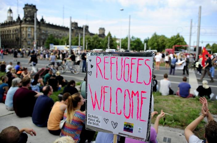 """Anti-racism protesters sit behind a banner reading """"Refugees Welcome"""" during a rally on August 29, 2015 in Dresden (AFP Photo/Robert Michael)"""
