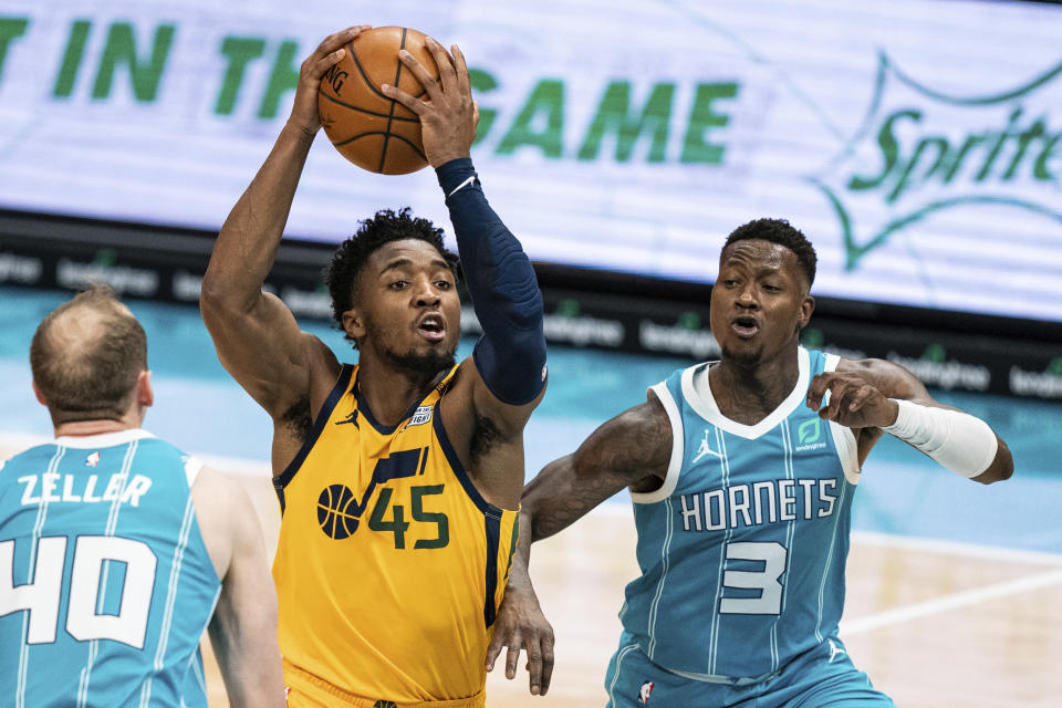 Utah Jazz guard Donovan Mitchell (45) drives to the basket while guarded by Charlotte Hornets center Cody Zeller (40) and guard Terry Rozier (3) during the second half of an NBA basketball game in Charlotte, N.C., Friday, Feb. 5, 2021. (AP Photo/Jacob Kupferman)