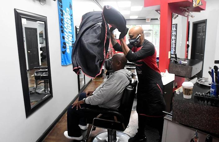 Barber Sean Richardson of Universal Cuts flips a barbers apron over customer Manny Golfe prior to a a haircut on Friday, May 22, 2020.