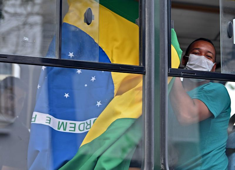 A Brazilian citizen shows a national flag from a bus taking him and others to the Jorge Chavez international airport in Callao, outside the Brazilian consulate in Lima, on March 20, 2020, due to coronavirus lockdown. - Some 400 Brazilian citizens are being repatriated after remaining stranded due to the closure of borders and the mandatory quarantine decreed by the Peruvian government as a preventive measure against the coronavirus pandemic. 263 people have tested positive and four have died in Peru so far from the new coronavirus, COVID-19. (Photo by Cris BOURONCLE / AFP) (Photo by CRIS BOURONCLE/AFP via Getty Images)