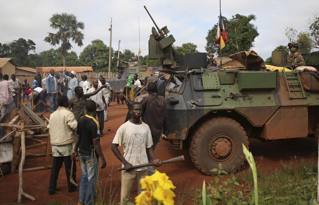 Men stand facing French soldiers as they block a road which French army vehicles were travelling on, during a protest in Bambari May 22, 2014.  REUTERS/Goran Tomasevic (CENTRAL AFRICAN REPUBLIC - Tags: CIVIL UNREST POLITICS MILITARY)