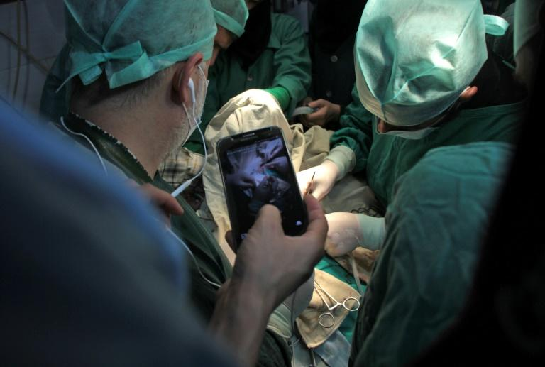 A surgeon holds a cell phone during surgery as he awaits a real-time consultation in Douma, a rebel-held town in the Eastern Ghouta region on October 11, 2017