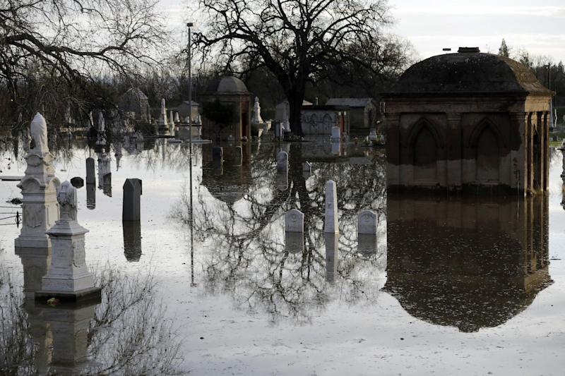 Graves are submerged in floodwaters at a cemetery downstream from a damaged dam Wednesday, Feb. 15, 2017, in Marysville, Calif. The Oroville Reservoir is continuing to drain Wednesday as state water officials scrambled to reduce the lake's level ahead of impending storms. (AP Photo/Marcio Jose Sanchez)