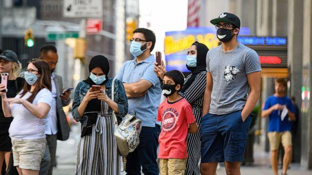 PHOTO: People wear protective face masks outside Radio City Music Hall as New York City moves into Phase 3 of re-opening following restrictions imposed to curb the coronavirus pandemic on July 12, 2020. (Noam Galai/Getty Images)