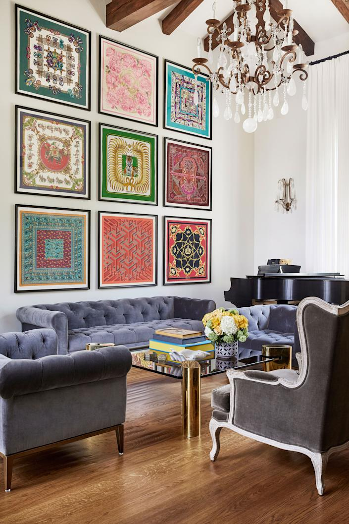 "<div class=""caption""> Designer Reza Farahan utilized the living room's substantial height by positioning a grid of nine vintage <a href=""https://www.hermes.com/us/en/"" rel=""nofollow noopener"" target=""_blank"" data-ylk=""slk:Hermès"" class=""link rapid-noclick-resp"">Hermès</a> scarves above the <a href=""https://rh.com/"" rel=""nofollow noopener"" target=""_blank"" data-ylk=""slk:RH"" class=""link rapid-noclick-resp"">RH</a> couch. The coffee table is a vintage Karl Springer made out of brass and smoked glass. Farahan custom-designed the rock crystal chandelier and sconces. </div>"