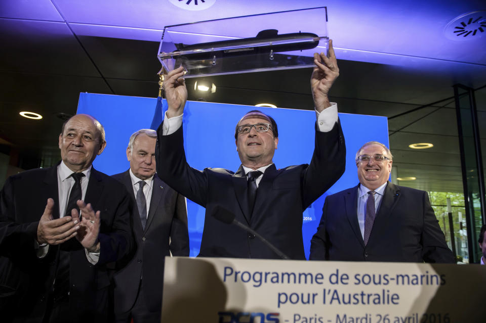 FILE - In this Tuesday, April 26, 2016 file photo, French President Francois Hollande, center, shows off a model of a submarine given by DCNS CEO Herve Guillou, right, in Paris, France. A round of free trade talks between the European Union and Australia has been postponed in the wake of a dispute over Canberra's decision to cancel a multibillion-euro French submarine deal. The 12th round of talks was scheduled to take place later this month. Australia had signed the 90 billion Australian dollar ($66 billion) deal in 2016 with French majority state-owned Naval Group in 2016 to build 12 conventional diesel-electric submarines. But Australia canceled the deal last month as part of an alliance with the United States and Britain. (Christophe Petit Tesson/Pool Photo via AP, File)