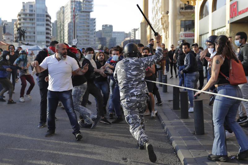 A police officer raises his baton to anti-government protesters during clashes during a protest in downtown Beirut, Lebanon, Tuesday, Nov. 19, 2019. Scuffles have broken out in central Beirut as hundreds of anti-government protesters tried to prevent lawmakers from reaching Parliament. (AP Photo/Hassan Ammar)