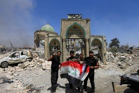 Members of the Counter Terrorism Service pose for a picture with an Iraqi flag in front of the ruins of Grand al-Nuri Mosque at the Old City in Mosul
