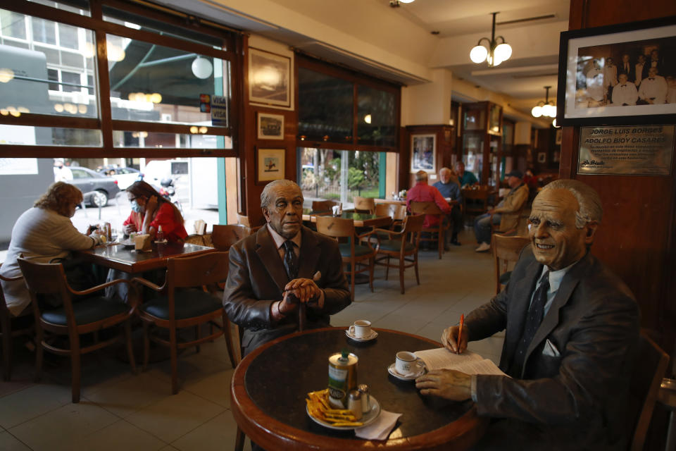 "Statues of Argentine writer Adolfo Bioy Casares, right, and Jorge Luis Borges, sit at a table at La Biela restaurant in Buenos Aires, Argentina, Tuesday, Nov. 10, 2020. At least four of the city's more than 70 officially recognized ""cafe notables"" have closed since a quarantine to curb the spread of the new coronavirus was announced on March 20 and others are hanging by a thread after months of revenues near zero. (AP Photo/Natacha Pisarenko)"