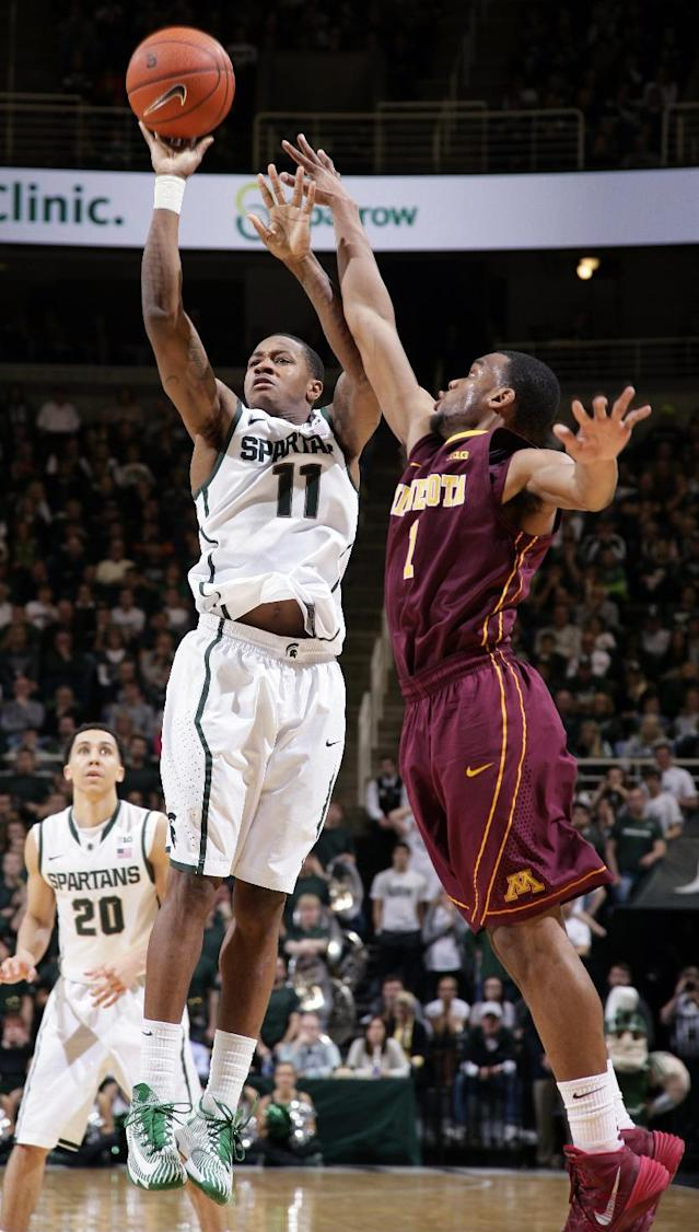 Michigan State's Keith Appling (11) shoots against Minnesota's Andre Hollins (1) during the second half of an NCAA college basketball game, Saturday, Jan. 11, 2014, in East Lansing, Mich. Michigan State won 87-75 in overtime. (AP Photo/Al Goldis)
