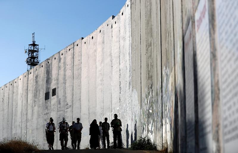 (FILES) A group of foreign Christian visitors pray as they walk along Israel's controversial separation barrier, which divides the West Bank from Jerusalem, on July 7, 2017 in the biblical West Bank town of Bethlehem